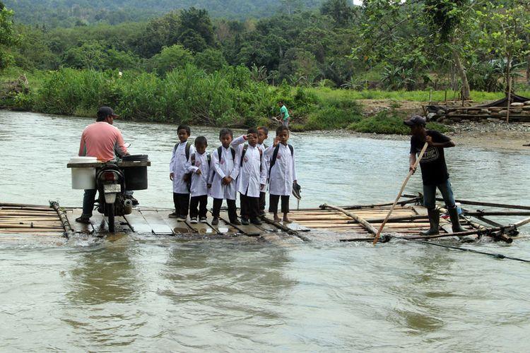 Sejumlah siswa menumpang rakit bambu untuk menyeberangi Sungai Mongiilo di Kecamatan Bulango Ulu Kabupaten Bone Bolango