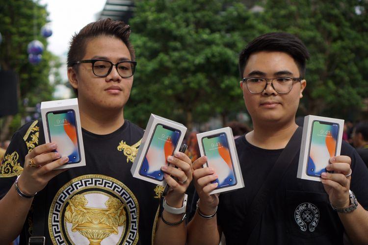 Pembeli pertama iPhone X di Apple Store Singapura Kittiwat Wang (kiri), dan temannya, Supakorn Rieksiri, menunjukkan empat unit iPhone X yang mereka beli, Jumat (3/11/2017).