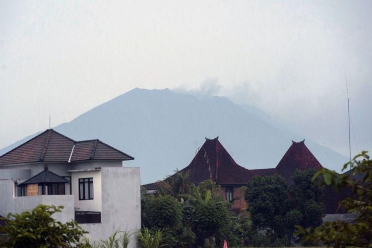 Asap kelabu menyembur dari puncak Gunung Agung, terpantau dari Kabupaten Gianyar, Bali, Selasa (21/11/2017). Pusat Vulkanologi dan Mitigasi Bencana Geologi menyatakan Gunung Agung meletus pukul 17.05 Wita dengan ketinggian asap mencapai 700 meter.(ANTARA FOTO/NYOMAN BUDHIANA)