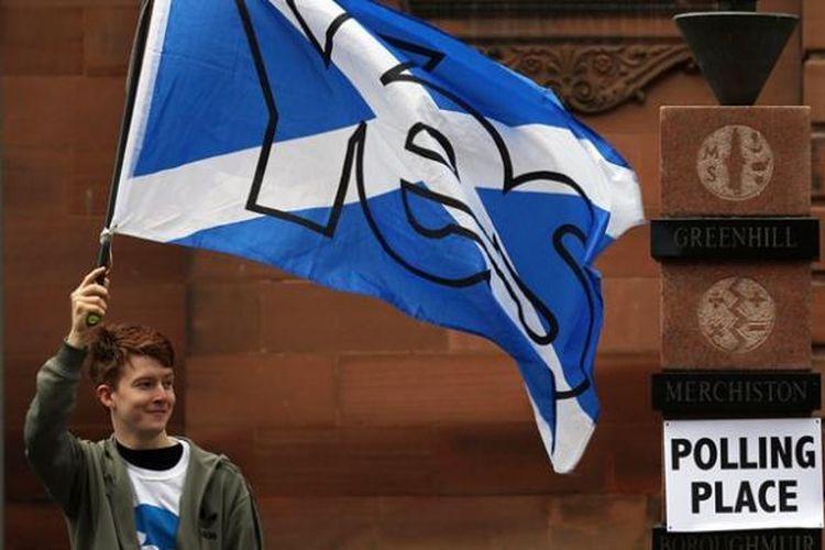Seorang pemuda membawa bendera Skotlandia di dekat sebuah TPS sesaat sebelum referendum dimulai. Referendum yang digelar Kamis (18/9/2014) ini akan menentukan apakah Skotlandia akan menjadi sebuah negara independen atau tetap di bawah bendera Inggris Raya.