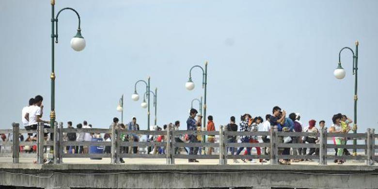 Pengujung menikmati pemandangan lepas pantai dari Dermaga Pantai Festival, Taman Impian Jaya Ancol, Jakarta Utara, Minggu (21/4/2013). Kawasan tersebut menjadi salah tempat pilihan warga Jakarta dan luar Jakarta yang ingin berwisata menikmati suasana pantai dengan nyaman.