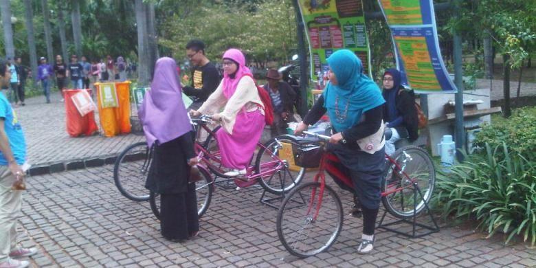 Pengunjung tengah mencoba sepeda yang bisa mencharge telepon genggam di Festival taman di Taman Cattleya, Tomang, Jakarta Barat, Sabtu (19/10/2013)