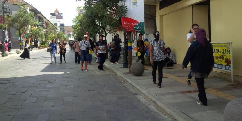 Wisatawan lokal dan asing sedang menikmati Braga di pagi hari dengan jalan kaki.