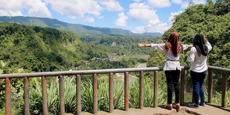 Dua wisatawan asal Pekanbaru, Riau, menikmati pemandangan dari puncak Janjang Seribu, Kota Bukittinggi, Sumatera Barat, Sabtu (25/4/2015). Potensi wisata, baik alam maupun budaya, yang sangat besar menjadi sektor penting dalam menunjang pembangunan Bukittinggi. Sektor tersebut menyumbang sekitar 62 persen bagi pendapatan asli daerah kota yang terkenal dengan ikon Jam Gadang ini.
