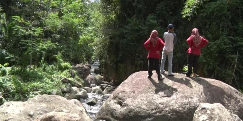 Wisatawan menikmati pemandangan sungai berbatu di kawasan di desa wisata Sawahan, Kecamatan Watulimo, Kabupaten Trenggalek, Jawa Timur.