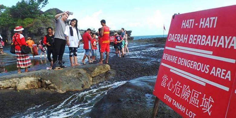 Wisatawan berfoto di area pantai di depan Pura Luhur Tanah Lot, Kabupaten Tabanan, Bali, Minggu (12/6/2016).