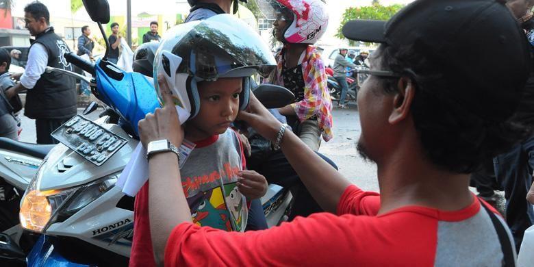 Kutu Community membagikan helm gratis untuk anak-anak di jalan raya.