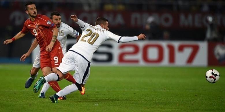 Penyerang Makedonia, Ilija Nestrovoski, melepaskan umpan saat dikawal pemain Italia, Federico Bernardeschi, pada laga di Skopje, Minggu (9/10/2016).