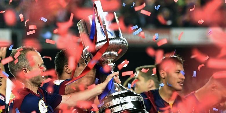 Gelandang Barcelona, Andres Iniesta, mengangkat trofi Copa del Rey seusai partai final kontra Athletic Bilbao di Stadion Camp Nou, 30 Mei 2015.