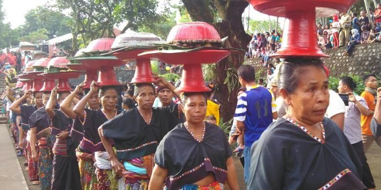Para perempuan suku Sasak membawa dulang berisi ketupat dan hasil bumi, sebelum perang topat dimulai. (KOMPAS.com/ Karnia Septia)