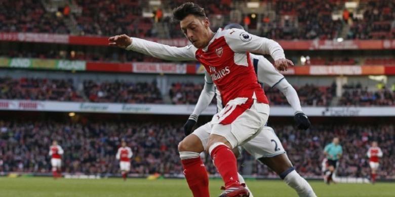 Gelandang Arsenal, Mesut Oezil, berduel dengan pemain West Bromwich Albion, Allan Nyom, dalam lanjutan Premier League di Stadion Emirates, Senin (26/12/2016).