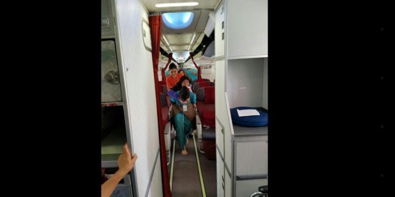 Seorang pramugari Garuda Indonesia menggendong penumpang lanjut usia beberapa waktu lalu. Foto ini menjadi viral di media sosial.