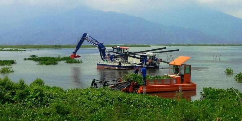 Dua kapal Aquatic tengah bekerja mengambil enceng gondok di perairan Rawapening, tepatnya di dekat dermaga Sumurup, desa Asinan, Bawen, Kabupaten Semarang, Rabu (11/1/2017) siang.