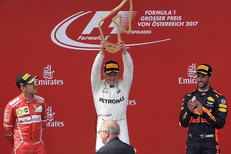 Pebalap Mercedes, Valtteri Bottas (tengah), mengangkat trofi kemenangannya pada balapan GP Austria di Red Bull Ring, Spielberg, Austria, Minggu (9/7/2017).