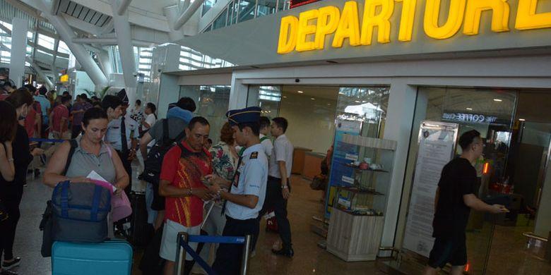 Petugas memeriksa tiket penumpang di Bandara Ngurah Rai Bali, Rabu (29/11/2017). Berdasarkan hasil rapat evaluasi kondisi terkini Gunung Agung yang kondisinya sudah turun dari merah ke oranye sehingga Bandara Ngurah Rai Bali dibuka kembali seperti biasa sejak pukul 15.00 Wita.