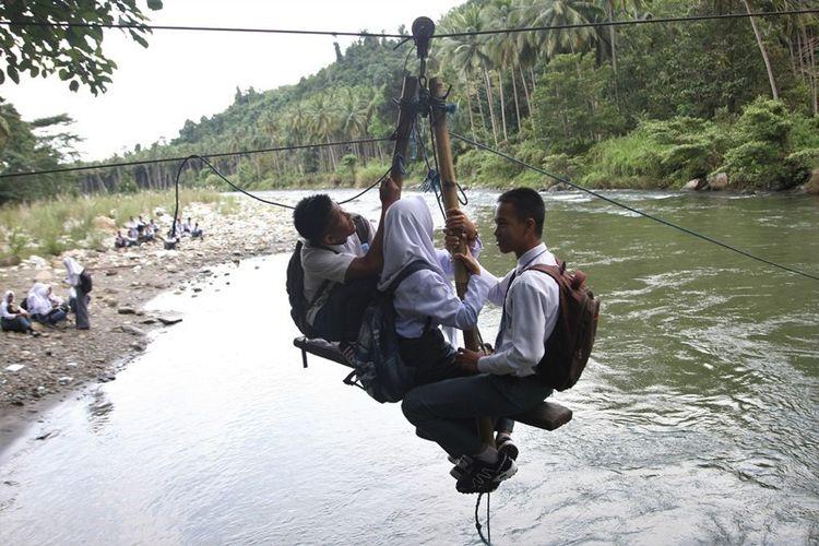 Beberapa pelajar menyeberang dengan tali penyeberangan darurat di Sungai Ranteangin, Desa Maroko ke Desa Tinokari, Wawo, Kolaka Utara, Sulawesi Tenggara, Jumat (28/7). Warga di Kecamatan Wawo hanya mengandalkan tali penyeberangan darurat untuk ke rumah dan ke kebunnya.