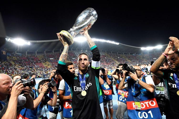 Bek Real Madrid, Sergio Ramos, mengangkat trofi Piala Super Eropa yang mereka raih setelah menang 2-1 atas Manchester United dalam pertandingan di Philip II Arena, Skopje, Selasa (8/8/2017).