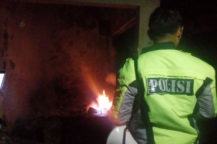 Petugas kepolisian mengawal proses pendinginan kios-kios yang terbakar