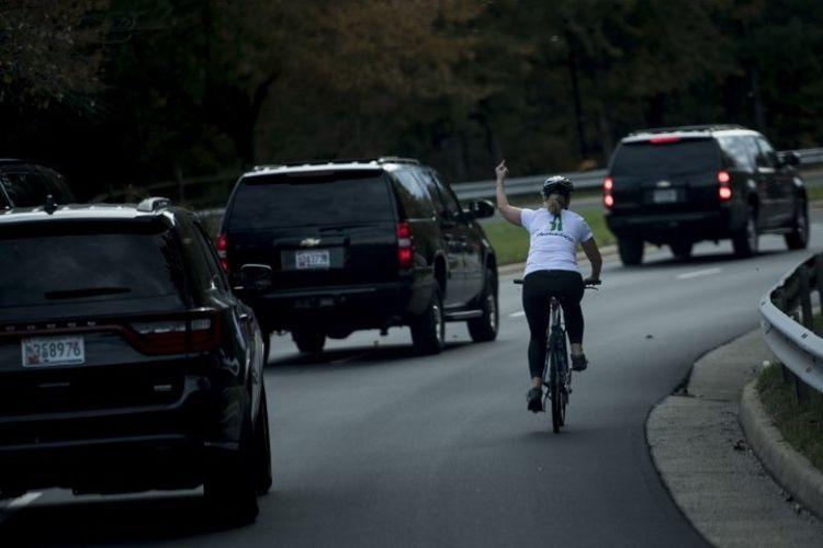 Seorang perempuan yang tengah mengendarai sepeda mengacungkan jari tengahnya ke arah rombongan Presiden AS Donald Trump yang baru saja selesai bermain golf.