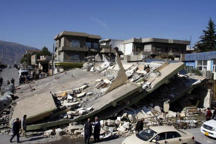 Orang-orang mengerumuni sebuah gedung bertingkat yang hancur akibat gempa berkekuatan 7,3 SR, di perbatasan Irak-Iran, Senin (13/11/2017). (AFP/Shwan Mohammed) SHWAN MOHAMMED