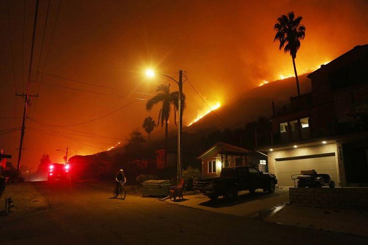 Peseoada melewati jalanan di dekat kobaran Api Thomas, pada Kamis (7/12/2017). di La Conchita, California. (AFP/Mario Tama)