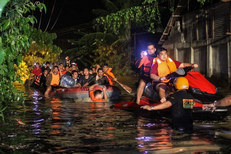 Petugas penyelamat mengevakuasi penduduk yang terkena banjir di Davao di pulau Mindanao, Filipina selatan, pada Jumat (22/12/2017), setelah badai tropis Tembin menyebabkan hujan lebat di seluruh pulau. (AFP/Manman Dejeto)