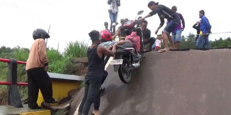 Akibat banjir yang memutuskan Jembatan Sungai Rungau di Jalan Trans Kalimantan, Kabupaten Seruyan, Kalimantan Tengah, warga harus menggotong sepeda motornya untuk melintass