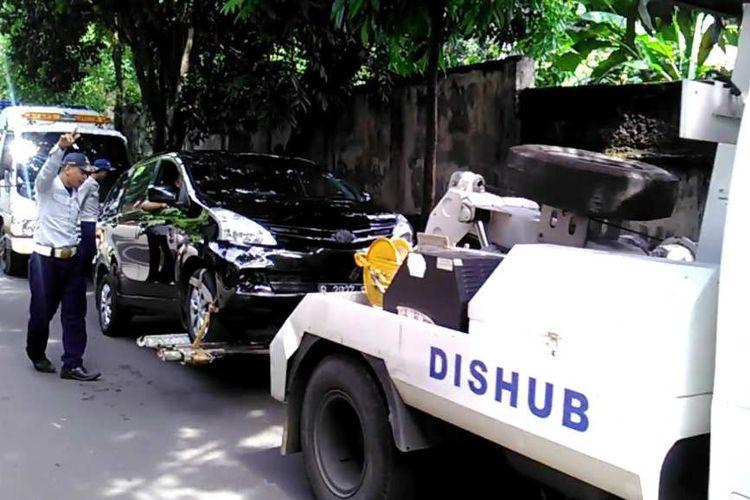 Mobil yang terparkir di pinggir Jalan Nipah, diderek petugas Dinas Perhubungan karena pengendara parkir sembarangan dan tidur dalam mobil, Rabu (15/11/2017).