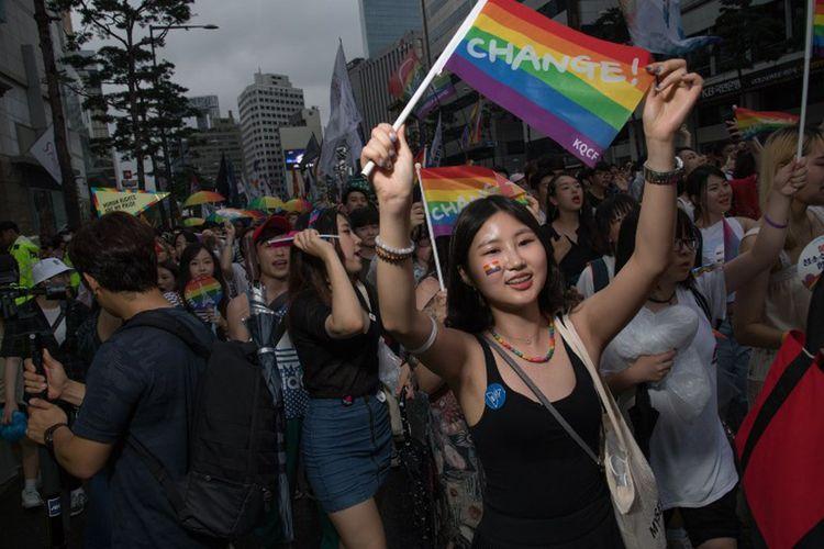 Seorang peserta aksi untuk hak kaum lesbian, gay, biseksual, dan transgender (LGBT) di Kota Seoul. Korea Selatan, Sabtu (15/7/2017), mengibarkan bendera pelangi.  Ribuan orang ambil bagian dalam aksi ini dengan bernyanyi, dan menari, tanpa peduli dengan hujan dan protes kelompok Kristen konservatif.