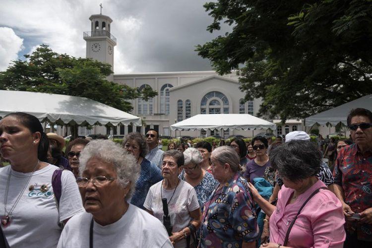 Umat Katolik di Guam, berkumpul di Ibu Kota Hagatna untuk menghadiri acara doa bersama untuk perdamaian, Minggu (13/8/2017). (AFP/ED JONES)