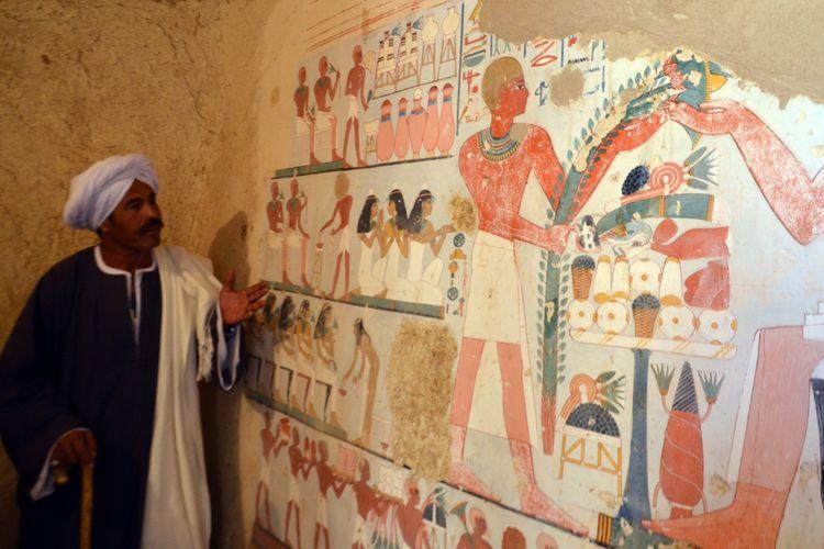 Seorang pekerja Mesir berdiri di samping lukisan yang ditemukan di Kampp 161 pada December 9, 2017. / AFP PHOTO / STRINGER