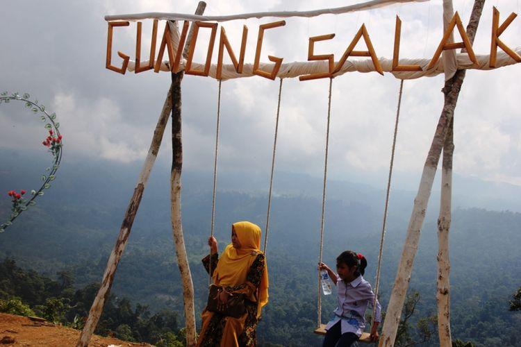 Warga bermain ayunan di destinasi wisata Rindu Alam, kawasan Gunung Salak, Aceh Utara.
