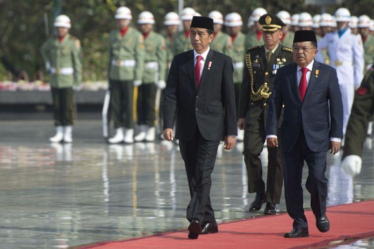 Presiden Joko Widodo (kiri) berjalan bersama Wakil Presiden Jusuf Kalla (kanan) sebelum memimpin  Upacara Ziarah Nasional di Taman Makam Pahlawan Kalibata, Jakarta, Jumat (10/11/2017). Upacara tersebut dilaksanakan sebagai bentuk penghormatan terhadap jasa pahlawan dan mengenang pertempuran 10 November di Surabaya. ANTARA FOTO/Rosa Panggabean/ama/17.