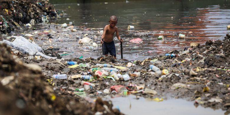 Seorang anak mencari sampah berupa besi di Kanal Banjir Barat (KBB) sungai Ciliwung di Tanah Abang, Jakarta Pusat, Senin (11/9/2017). Pengerukan lumpur dilakukan untuk memperlancar aliran air sungai serta mengantisipasi datangnya musim hujan yang mengakibatkan banjir yang kerap terjadi di Jakarta.