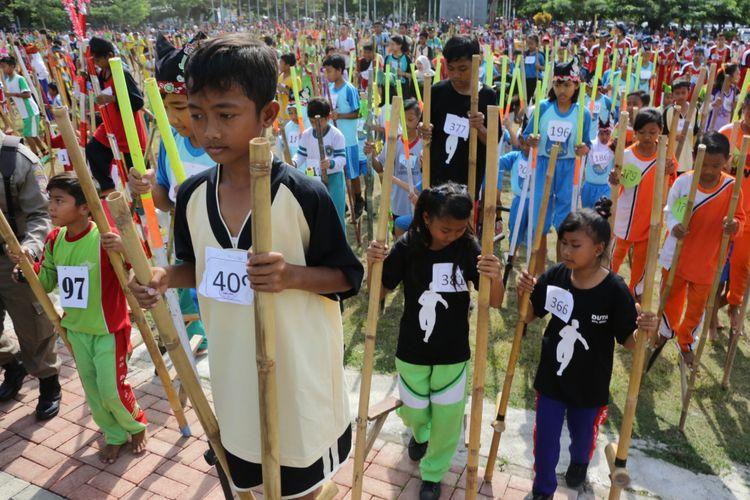 Peserta Festival Permainan Anak Banyuwangi 2016 bersiap melakukan parade dengan berjalan menggunakan egrang bambu. Akhir pekan ini (22/7/2017), Banyuwangi kembali menggelar festival permainan tradisional yang melibatkan lebih dari 5 ribu anak dari 25 kecamatan.