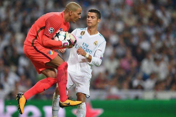 Kiper APOEL, Boy Waterman, dengan sigap menangkap bola yang coba dikejar penyerang Real Madrid, Cristiano Ronaldo, pada pertandingan Liga Champions di Stadion Santiago Bernabeu, Rabu (13/9/2017).