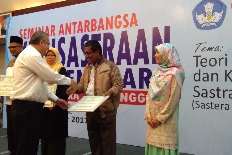Ketua Majelis Sastra Asia Tenggara sekaligus Kepala Badan Bahasa Kemendikbud Dadang Sunendar memberikan penghargaan Sastrawan Muda Asia Tenggara kepada Norman Erikson Pasaribu yang diwakili oleh ayahnya di Hotel Sari Pan Pasifik Jakarta, Senin (11/09/17).