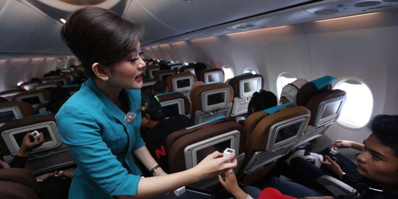 Pramugari maskapai Garuda Indonesia membagikan coklat geratis kepada penumpang saat  penerbangan bertajuk Kartini Flight di perjalanan menuju Bandara Minangkabau Padang, Sumatra Barat, Jumat (21/4/2017). Garuda Indonesia gelar Kartini Flight dalam rangka menyambut hari Kartini, seluruh petugas penerbangan dari Pilot, Pramugari hingga teknisi adalah perempuan.