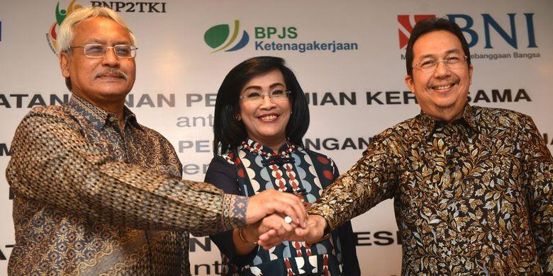 Direktur Hubungan Kelembagaan dan Transaksional Perbankan BNI Adi Sulistyowati  (tengah) berjabat tangan bersama Deputi Penempatan TKI BNP2TKI Agustin Subiantoro (kiri) dan Direktur Perluasan Kepesertaan dan Hubungan Antar Lembaga BPJS Ketenagakerjaan E Ilias Lubis (kanan) saat penandatanganan kerja sama di Jakarta, Senin (7/8/2017). BNI bersama Badan Nasional Penempatan dan Perlindungan Tenaga Kerja Indonesia (BNP2TKI) dan BPJS Ketenagakerjaan bekerja sama untuk penerbitan Kartu Pekerja Indonesia (KPI) co-branding, Layanan Cash Management, fasilitas kredit untuk TKI dan layanan jasa perbankan guna mendukung Program Jaminan Sosial bagi TKI.  ANTARA FOTO/Prasetyo Utomo/aww/17.