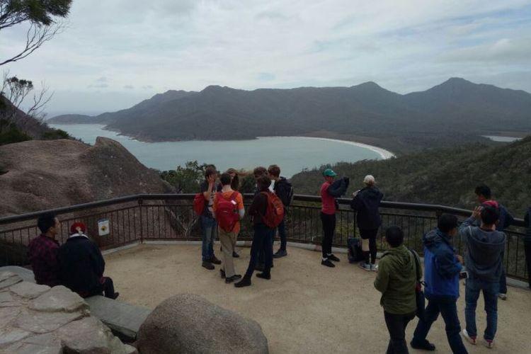 Para wisatawan disuguhi pemandangan indah ke arah Teluk Wineglass, Tasmania dari ketinggian 240 meter di atas permukaan laut.