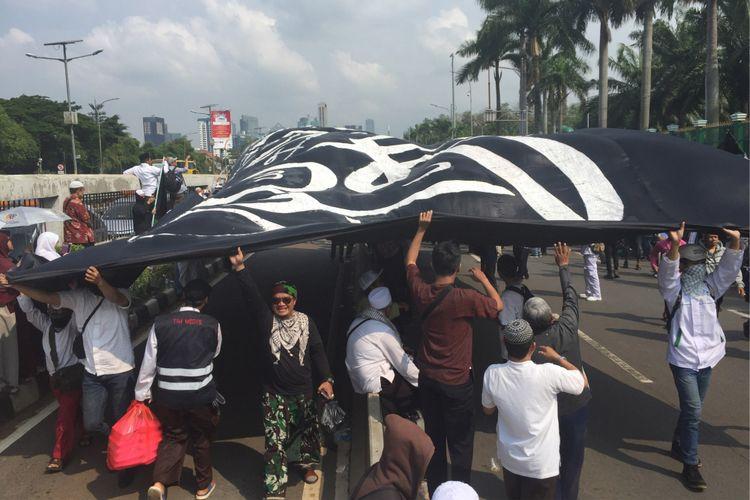 Massa peserta Aksi 299 membawa bendera raksasa sambil meneriakkan kata khilafah di Jalan Gatot Subroto, depan komplek gedung MPR/DPR pada Jumat (29/9/2017) siang.
