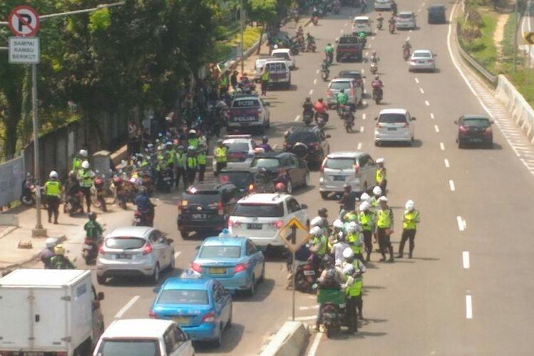 Polisi melakukan penindakan terhadap pengendara motor yang masih nekat melintas di JLNT Casablanca, Selasa (25/7/2017).