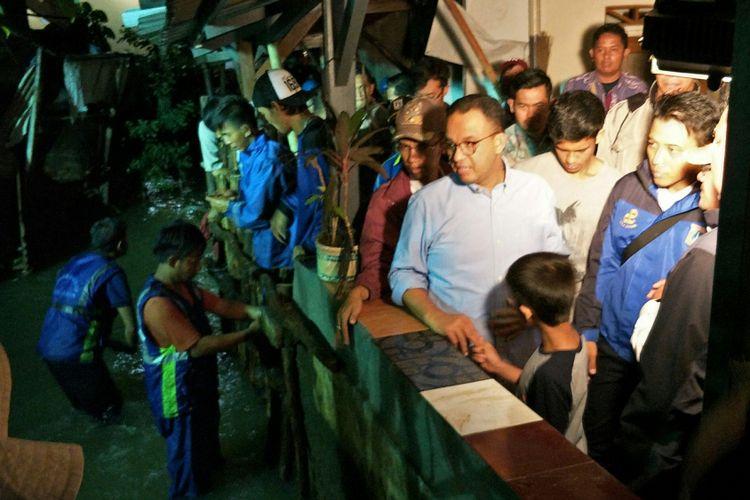 Gubernur DKI Jakarta Anies Baswedan meninjau tanggul yang jebol di RT 14 RW 06 Kelurahan Jatipadang, Pasar Minggu, Jakarta Selatan, Rabu (20/12/2017) malam.