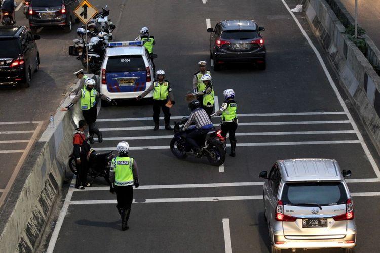 Polisi melakukan razia sepeda motor yang nekat menerobos ke jalan layang non tol (JLNT) Kampung Melayu-Tanah Abang, Jakarta, Selasa (25/7/2017). Pengendara motor masih nekat memasuki dan melintasi JLNT tersebut baik dari arah Tanah Abang maupun Kampung Melayu. KOMPAS IMAGES/KRISTIANTO PURNOMO