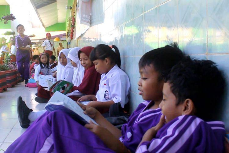 Para pelajar terpaksa belajar di lantai, karena ruangan kelas yang biasa mereka gunakan disegel pemilik lahan.