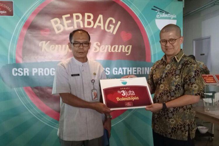 William Henley selaku CEO dan direktur PT IndoSterling menyerahkan donasi sebesar Rp 3 juta ke Panti Sosial Bina Grahita Belaian Kasih di acara konferensi pers Bakmitopia di Kebon Jeruk, Jakarta Utara, Kamis (12/10/2017)