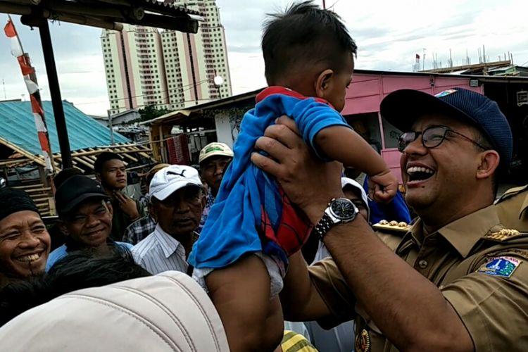 Gubernur DKI Jakarta, Anies Baswedan saat menggendong bayi bernama Muhammad Asa di Kampung Akuarium, Jakarta Utara, Senin (27/11/2017).