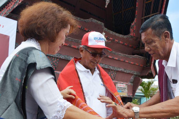 Kepala Desa Tomok Mangiring Sidabutar mengulosi Direktur Keuangan Pelindo 1 Farid Luthfi, Senin (15/11/2017)