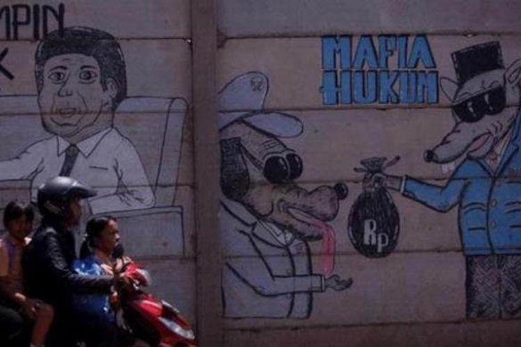 Warga melintas di dekat mural mengenai mafia hukum di Jalan Haji Koting, Kunciran Induk, Pinang, Tangerang, Banten, Sabtu (1/9/2012). Persoalan-persoalan politik dan hukum seperti mafia hukum yang kerap kali muncul membuat jengah masyarakat yang kemudian diekspresikan melalui mural.