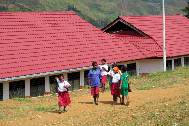 Sekelompok siswa SD Inpres Tiom berjalan pulang dari sekolahnya yang belum sepenuhnya memulai aktivitas belajar-mengajar di Kabupaten Lanny Jaya, Papua, Selasa (28/7/2015). Kabupaten pemekaran dari Jayawijaya pada tahun 2008 ini membutuhkan 200-300 guru TK/PAUD, SMP,dan SMA/SMK.